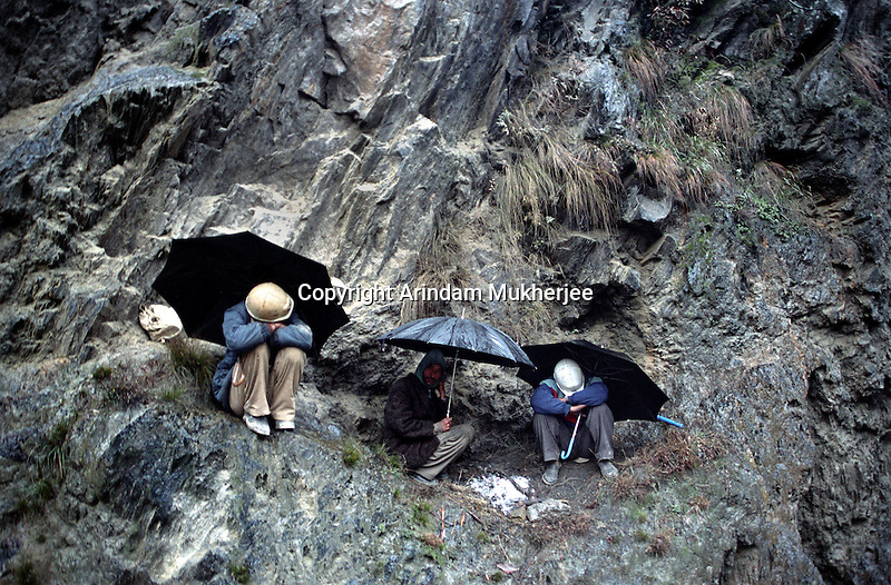 The workers of 'Beacon' , the border highway- makers, take rest at the venue of a land slide zone during a rainfall, Outskirts of Srinagar. Kashmir valley, India