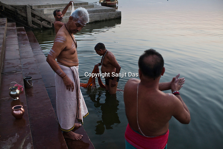 Religious Hindu priests offer prayers and take a bath at dawn on the ghats of Ganges in the ancient city of Varanasi in Uttar Pradesh, India. Photograph: Sanjit Das/Panos