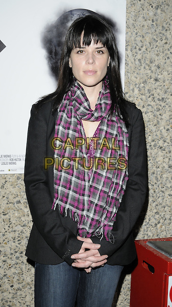 """NEVE CAMPBELL .The film premiere of """"Dirty Oil"""", Barbican Centre, London, England.March 15th 2010.half length black jacket red pink checked check scarf gingham plaid fringe jeans  denim.CAP/CAN.©Can Nguyen/Capital Pictures."""