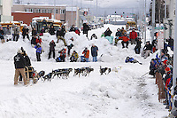 Saturday March 6 , 2010  Art Church takes the turn from 4th Avenue onto Cordova Street as spectaors line the snow berms in downtown Anchorage during the ceremonial start of the 2010 Iditarod
