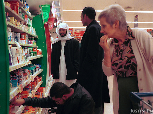 Bengladeshi youths shop in Oldham, a poor mill town in northern England where Muslims and Christians live in virtual apartheid...Oldham is scene of heavy rioting by Asians in the summer of 2001...Young muslims grow up separated from the indigenous society. They go to predominantly Asian schools and hang out with Asian friends. Often the only contact between the two communities is through uncertain glances on the street or in local tabloids. Although the atmosphere on the streets seems friendly, few people dare to step out of their own territory for fear of assault. Stuck in a Western society but feeling unwelcome and without many chances to escape from the ghetto, many youngsters seek identity in Islam...Many say they do not feel part of the British community, and the war in Afghanistan only confirmed the West's animosity. In this highly segregated pocket of Islam, the old and young, good and bad are pushed to the same fold by a shared sense of alienation in a Western society that they feel is oppressive - both locally and around the world. ..Photo by Justin Jin/Agentur Focus. Northern England, November 2001.