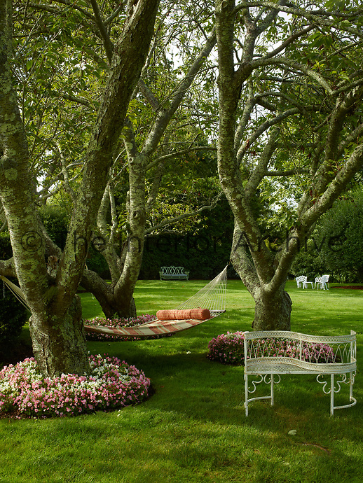 Flower beds of pretty pink and white flowers encircle the bases of trees. A hammock is strung between the trees and provides the perfect shady spot for relaxing in the garden.