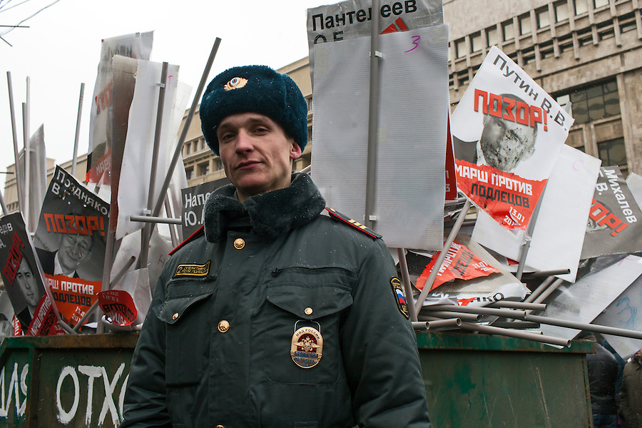 Moscow, Russia, 13/01/2013..Russian police guard a skip marked ?for garbage? that has been filled with portraits of President Vladimir Putin and other Russian politicians. Thousands of opposition protesters carried posters of President Vladimir Putin and members of the Russian parliament with the word ?Shame? written in red at a protest called the March Against The Scoundrels. The protest was against the new law banning the adoption of Russian children by Americans, widely seen as a response to the recently passed USA Magnitsky Act.