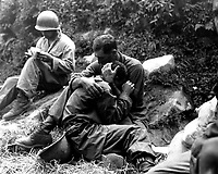 A grief stricken American infantryman whose buddy has been killed in action is comforted by another soldier. In the background a corpsman methodically fills out casualty tags, Haktong-ni area, Korea.  August 28, 1950.  Sfc. Al Chang. (Army)<br /> NARA FILE #  080-SC-347803<br /> WAR &amp; CONFLICT BOOK #:  1459