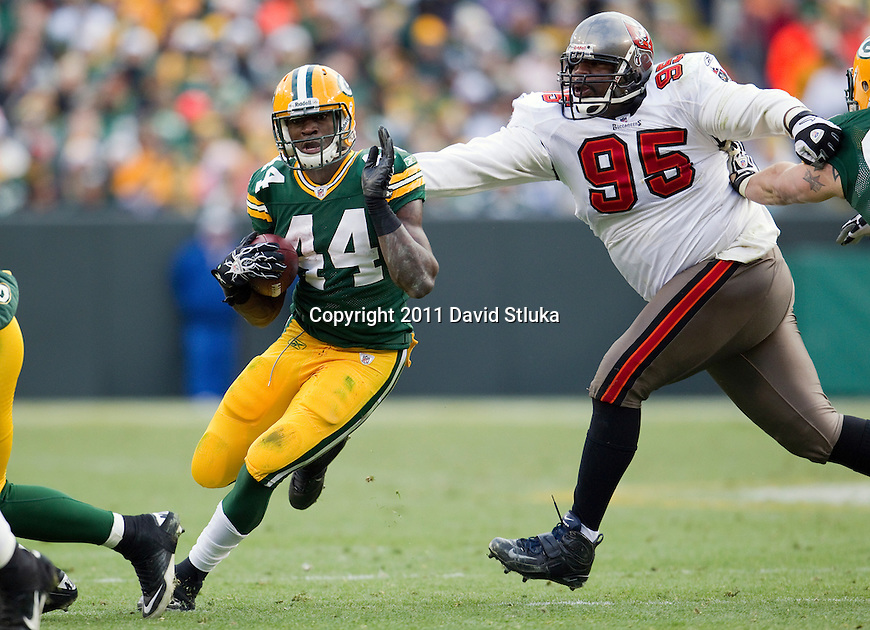 Green Bay Packers running back James Starks (44) runs past Tampa Bay Buccaneers defensive lineman Albert Haynesworth (95) during a Week 11 NFL football game on November 20, 2011 in Green Bay, Wisconsin. The Packers won 35-26. (AP Photo/David Stluka)