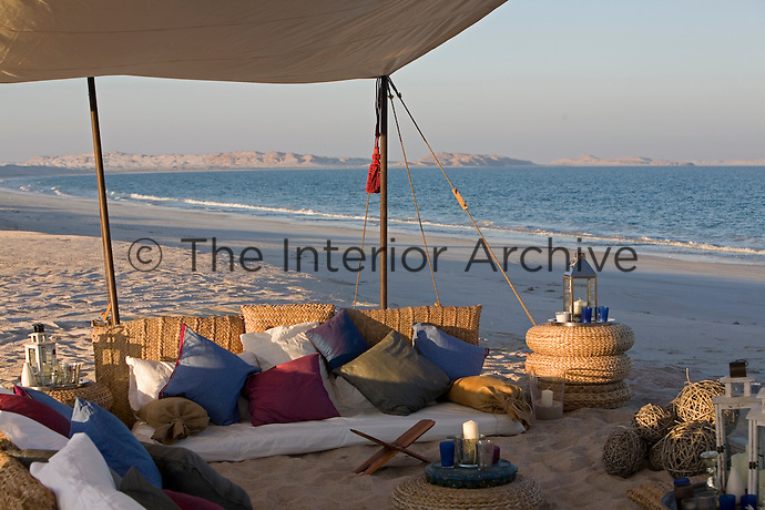 Woven straw cushions are used to create sofas and side tables in the beach camp's seating area under a canvas awning