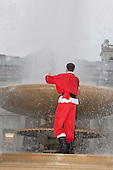 LONDON, ENGLAND - Santacon Santa falls in Trafalgar Square Fountain