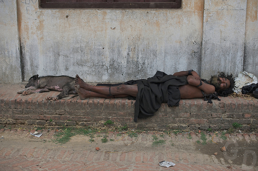 Man and his dog sleeping in the street, Bhaktapur, Layaku Nepal