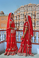 Indian women in color saris in fron to the Palace of the Wind or Hawa Mahal, Jaipur, India