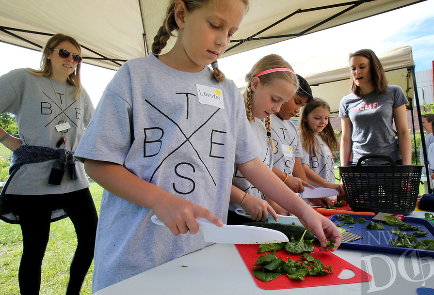 NWA Democrat-Gazette/DAVID GOTTSCHALK   Landry Clayton (from left) and Chloe Bryan, both fourth grade students at Butterfield Trail Elementary School, cut vegetables Tuesday, May 2, 2017, with classmates at the Apple Seeds Training Farm in Fayetteville. Two fourth grade classes from the school participated in a Farm Lab that included planting, harvesting and preparing a tzatziki and humus deep to eat.