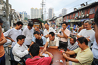 People crowd around a game of cards at an outdoor restaurant.