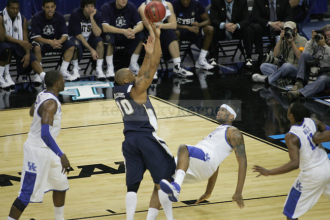 freshman forward DeMarcus Cousins falls to the ground after ETSU's Micah Williams goes for a basket during the second half of the UK men's basketball against East Tennessee State for the first round of the NCAA tournament at New Orleans Arena on Thursday, March 18, 2010. The Cats won 100-71 over the Bucs. Photo by Adam Wolffbrandt | Staff
