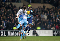 Cian Harries of Coventry City & Adebayo Akinfenwa of Wycombe Wanderers go for the ball during the The Checkatrade Trophy - EFL Trophy Semi Final match between Coventry City and Wycombe Wanderers at the Ricoh Arena, Coventry, England on 7 February 2017. Photo by Andy Rowland.