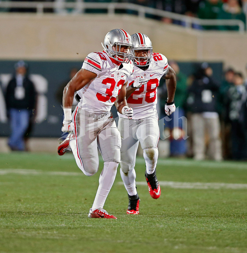 Ohio State Buckeyes linebacker Dante Booker (33) and Ohio State Buckeyes running back Warren Ball (28) on kickoff coverage against Michigan State Spartans at Spartan Stadium in East Lansing, Michigan on November 8, 2014.  (Dispatch photo by Kyle Robertson)