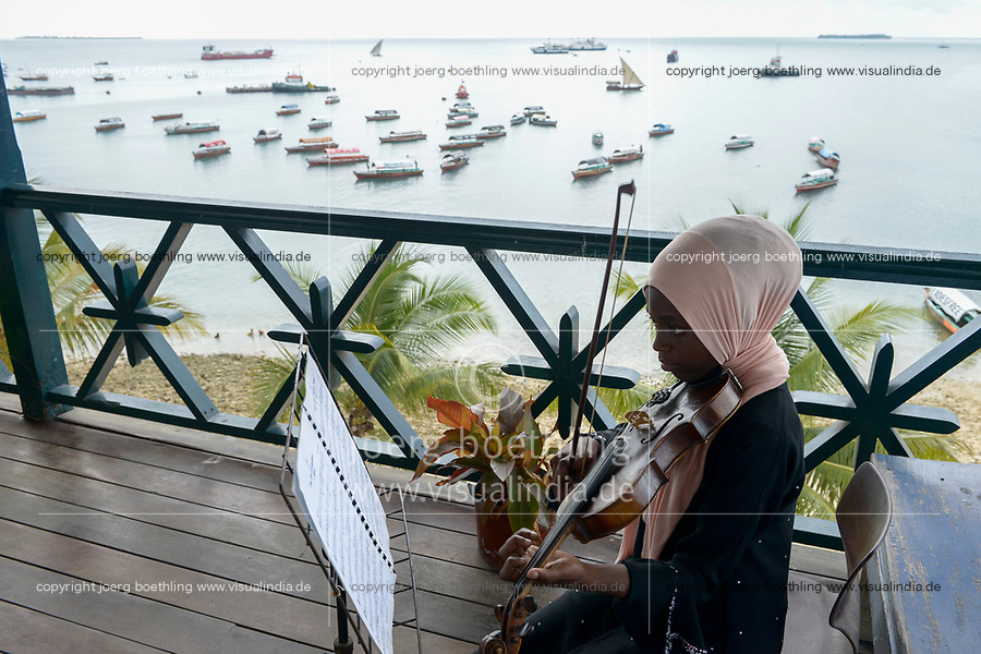 TANZANIA, Zanzibar, Stone town, Dhow countries music academy, girl plays violin on balcony with view to the indian ocean and harbour
