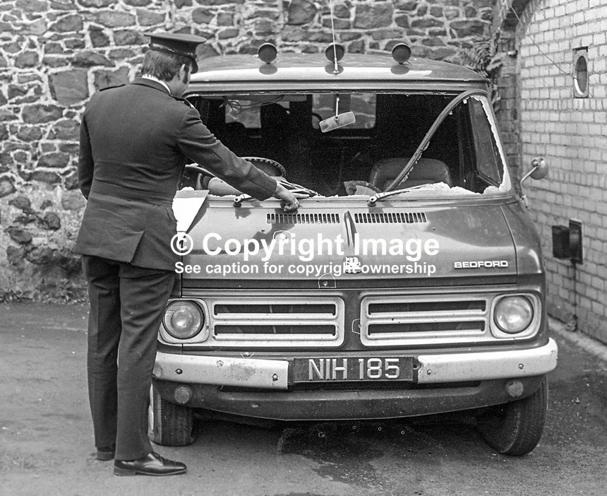 Policeman at Antrim RUC station with the minibus in which 17 year old  Henry Cunningham, a Protestant construction worker, from Carndonagh, Co Donegal, Rep of Ireland, was shot dead in a UVF gun attack on 10th August 1973. He was a front seat passenger in a minibus with a Rep of Ireland vehicle registration number. He was one of six workers, both Protestant & Roman Catholic, employed on a building site in Newtownabbey, on the outskirts of Belfast. Altogether 14 shots hit the minibus slightly injuring one other occupant. The Protestant paramilitary UVF would have assumed that all the occupants were Roman Catholic.  197308090541b..Copyright Image from Victor Patterson, 54 Dorchester Park, Belfast, United Kingdom, UK...For my Terms and Conditions of Use go to http://www.victorpatterson.com/Victor_Patterson/Terms_%26_Conditions.html