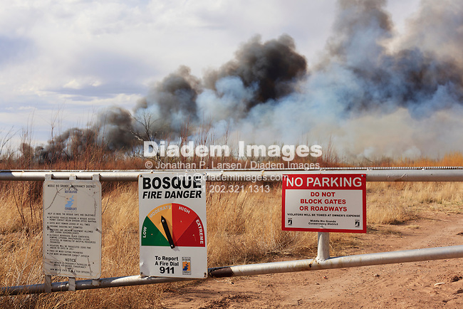 A fire danger sign and gate in rural New Mexico with wildfire burning in the background.