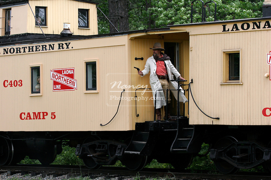 A cowboy defending an old steam train at gunpoint from a train robbery