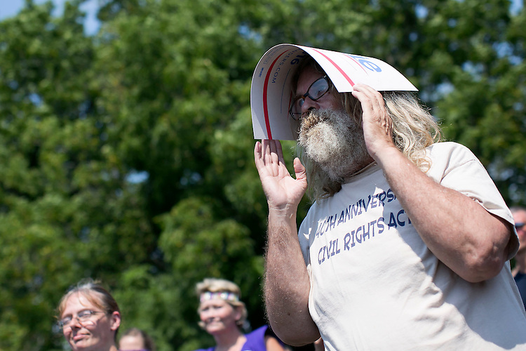 UNITED STATES - August 16: A man uses a Bernie Sanders for President poster to deflect the sun as he listens to Sen. Bernie Sanders, D-Vt., speak at the Scott County Democrats Picnic in the Park in Eldridge, Iowa, on Sunday, August 16, 2015. (Photo By Al Drago/CQ Roll Call)