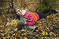Young girl hunter posing with ruffed grouse and her dog