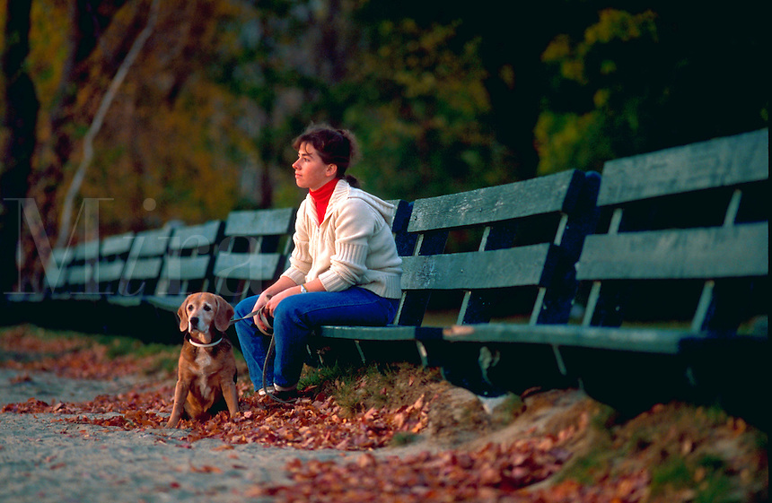 Woman sitting on a park bench with her dog.