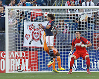 New England Revolution defender Kevin Alston (30) heads a cross clear as New England Revolution goalkeeper Bobby Shuttleworth (22) watches. In a Major League Soccer (MLS) match, the New England Revolution (blue/white) defeated Houston Dynamo (orange), 2-0, at Gillette Stadium on April 12, 2014.