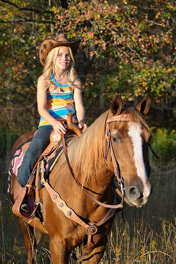 Young blonde cowgirl trail riding her chestnut horse in late evening golden light, wearing cowboy hat, focus on horse, Pennsylvania, PA, USA.
