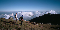 August 9th, 2004-Baugia, Timor-Leste-A young man and a local Timorese guide look out over the dramatic landscape from near the peak of Mt. Matebian.  Mt. Matebian 'Mountain of the Dead,' towers to the height of 1,871 meters and is the 2nd highest mountain in Timor-Leste.  Photograph by Daniel J. Groshong/Tayo Photo Group