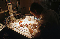 Premature infant in a high dependency intensive care cot in a special care baby unit. A doctor takes a blood sample for analysis. This image may only be used to portray the subject in a positive manner..©shoutpictures.com..john@shoutpictures.com