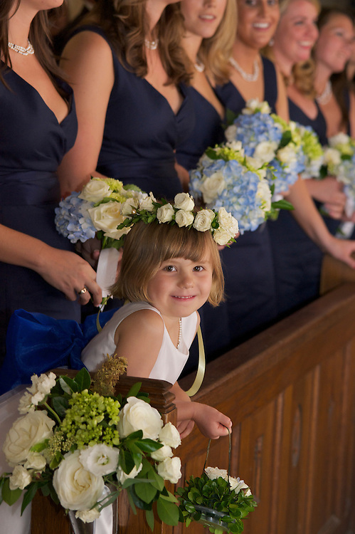 The flower girl with bridesmaids in the  background in the front pew of the church.