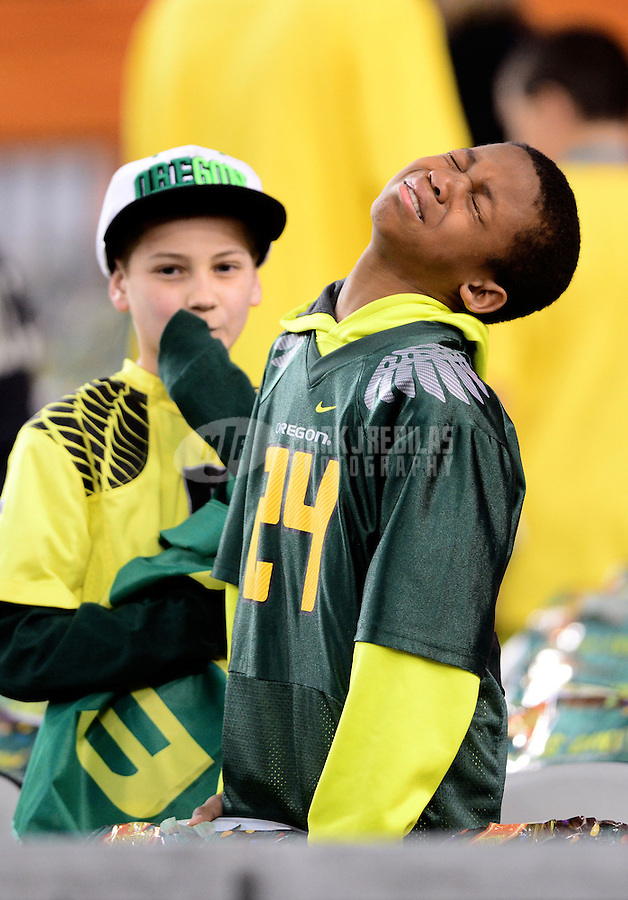 Jan. 3, 2013; Glendale, AZ, USA: A young Oregon Ducks fan wearing a Kenjon Barner jersey cries in the grandstands prior to the game against the Kansas State Wildcats during the 2013 Fiesta Bowl at University of Phoenix Stadium. Mandatory Credit: Mark J. Rebilas-