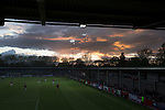The sun setting over Broadhurst Park, Manchester, the new home of FC United of Manchester during the second-half of the club's match against Benfica, champions of Portugal, which marked the official opening of their new stadium. FC United Manchester were formed in 2005 by fans disillusioned by the takeover of Manchester United by the Glazer family from America. The club gained several promotions and played in National League North in the 2015-16 season, but lost this match 1-0.