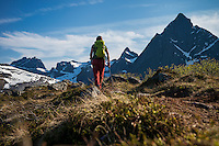 Female hiker hiking trail towards Flakstadtind mountain peak, Flakstadøy, Lofoten Islands, Norway