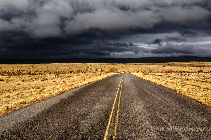 Sandoval County Road 279 lit by the sun shining through a break in the dark, stormy sky