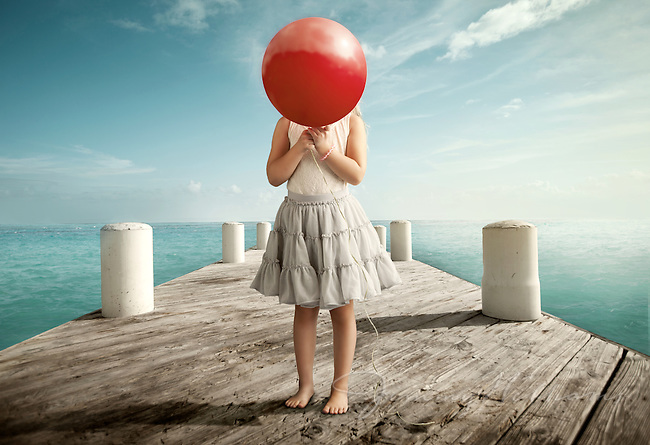 A girl hiding behind a red balloon.