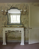 An antique painted console table and mirror arranged against walls lined in charmingly faded and peeling wallpaper