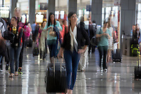 Businesswoman walking through the busy and crowded Austin–Bergstrom International Airport (ABIA) corridor, intentional motion blur.