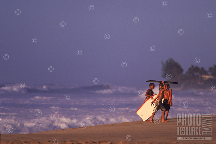 Keiki Bodyboarders in the winter evening at Ehukai Beach