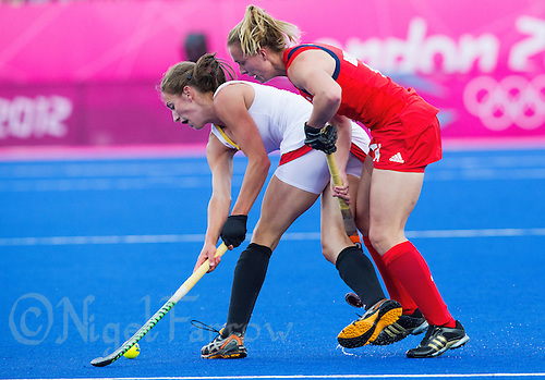 02 AUG 2012 - LONDON, GBR - Judith Vandemeiren (BEL) (left) of Belgium holds off a challenge from Laura Bartlett (GBR) (right) of Great Britain during the London 2012 Olympic Games preliminary round hockey match between the two teams at the Riverbank Arena in the Olympic Park at Stratford, Great Britain .(PHOTO (C) 2012 NIGEL FARROW)