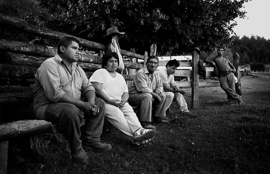 """Liquiñe Dam Project, Patagonia, Chile. Daniel Queupumil Fucha (left) and Nori Quintoman Trafipan (n.2 from the left) together with some of their fellow dam opposers. Daniel and Nori are among the main activists from the Mapuche community in Liquine fighting against the dam projects. Since the beginning of the battle they have become experts in all legal matters regarding indigenous populations and natural resources, with help from the Chilean human rights organization """"Observatorio Ciudadano""""."""
