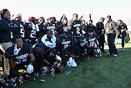 November 28, 2013  (Washington, DC) The H.D. Woodson Warriors gathers for a team photo with the game trophy after winning the 2013 DCIAA varsity football championship game November 28, 2013.  (Photo by Don Baxter/Media Images International)