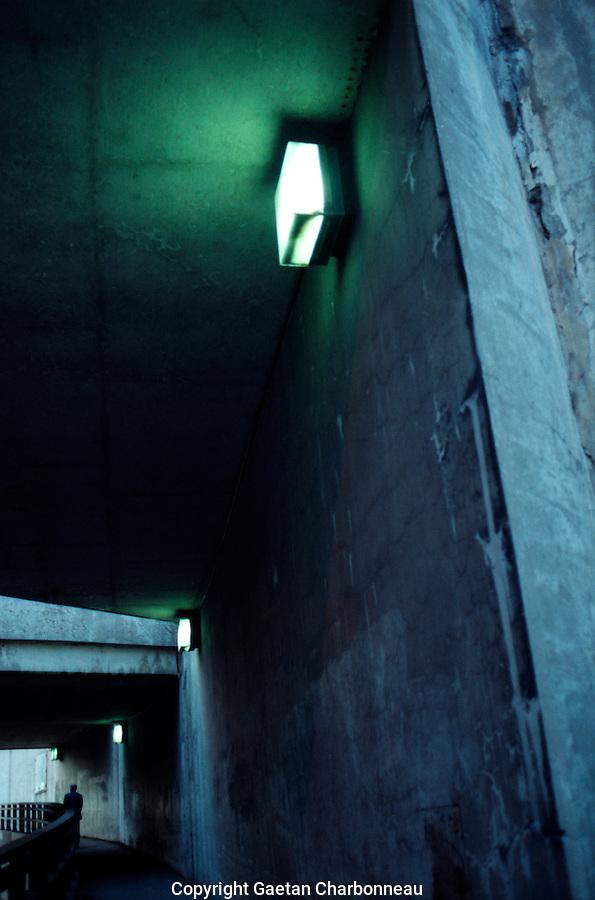 A worn blue concrete hallway lit with safety lights.
