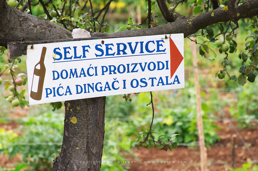 Sign at a winery saying Self Service Domaci Proizvodi, Pica Dingac i Ostala, inviting visitors to help themselves to tasting and buying the wine. Potmje village, Dingac wine region, Peljesac peninsula. Dingac village and region. Peljesac peninsula. Dalmatian Coast, Croatia, Europe.