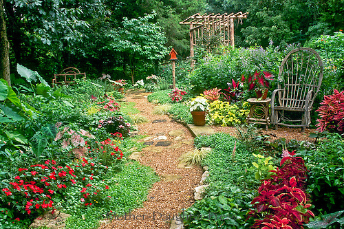 Gravel path through a shade garden alive with red and yellow flowers and ornamental plants leading to hand built archway and to the wood beyond