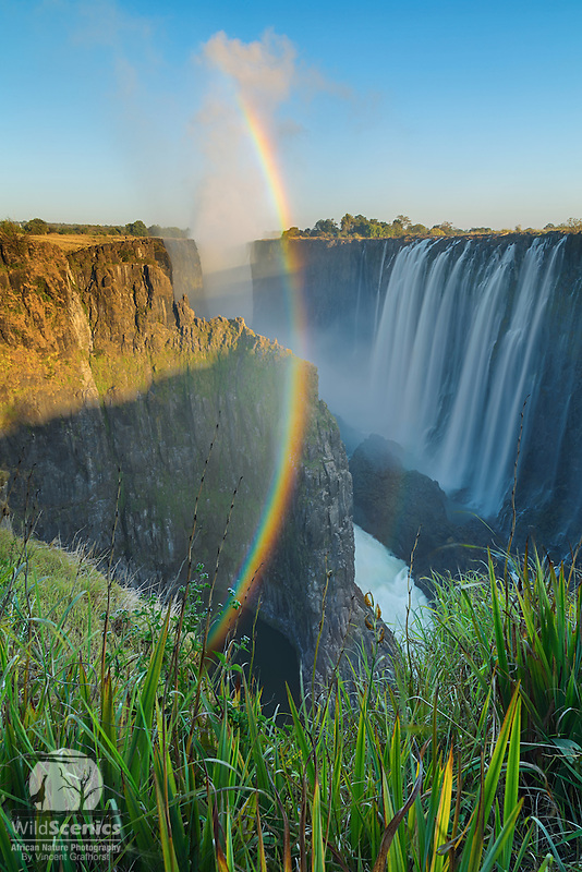 A magical sunrise scene with rainbow of the magnificent Victoria Water Falls in Zambia.<br />