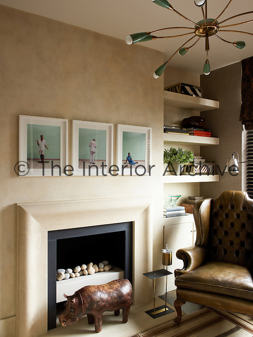 In the study three framed photographic prints are displayed above the contemporary fireplace next to a comfortable leather wing-backed chair