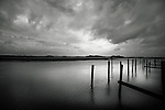 Quiet morning on Floridas Intracoastal Waterway, remnants of an old pier, that has rotted away, as a storm passed overhead.