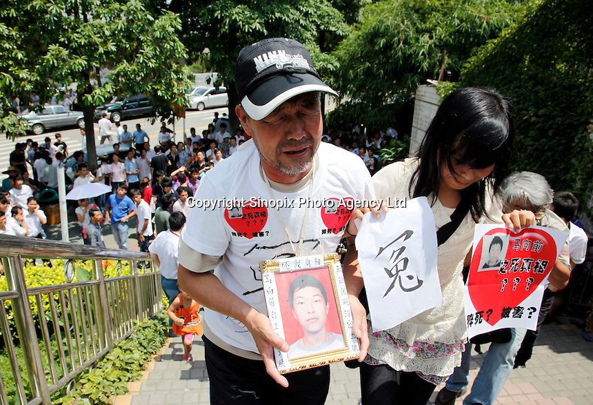 The grieving parents and sisters of Ma Xiangqian, who fell to his death earlier this year, cry outside Hon Hai Group's Foxconn plant in Shenzhen, China. Hon Hai is the parts supplier for many hi-tech companies around the world including Apple Inc., Hewlett-Packard Co. and Dell Inc. There have been 12 suicides at the company's 300 thousand employee strong factory complex in Shenzhen so far this year..26 May 2010