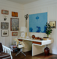 A framed collection of flint and a blue painting hang on the wood-panelled walls of the study furnished with a 1970s desk and chair