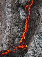 The bottom of this lava flow photograph looked to me like a snake facing to the right. In May 2015, the only way to reach flowing lava on the Big Island of Hawaii was by a 6 mile, round trip, walk through mud which was constant on the entire hike. Sometimes 1 inch and up to mid-calf at other times. If you go, hope for clouds or rain to make the glow more vibrant during the daytime. This hike must be done with a Hawaiian guide, not on your own. The process is to find the lava flow and wait for bulges where the lava breaks out and flows. Treat Madame Pele with respect at all times.